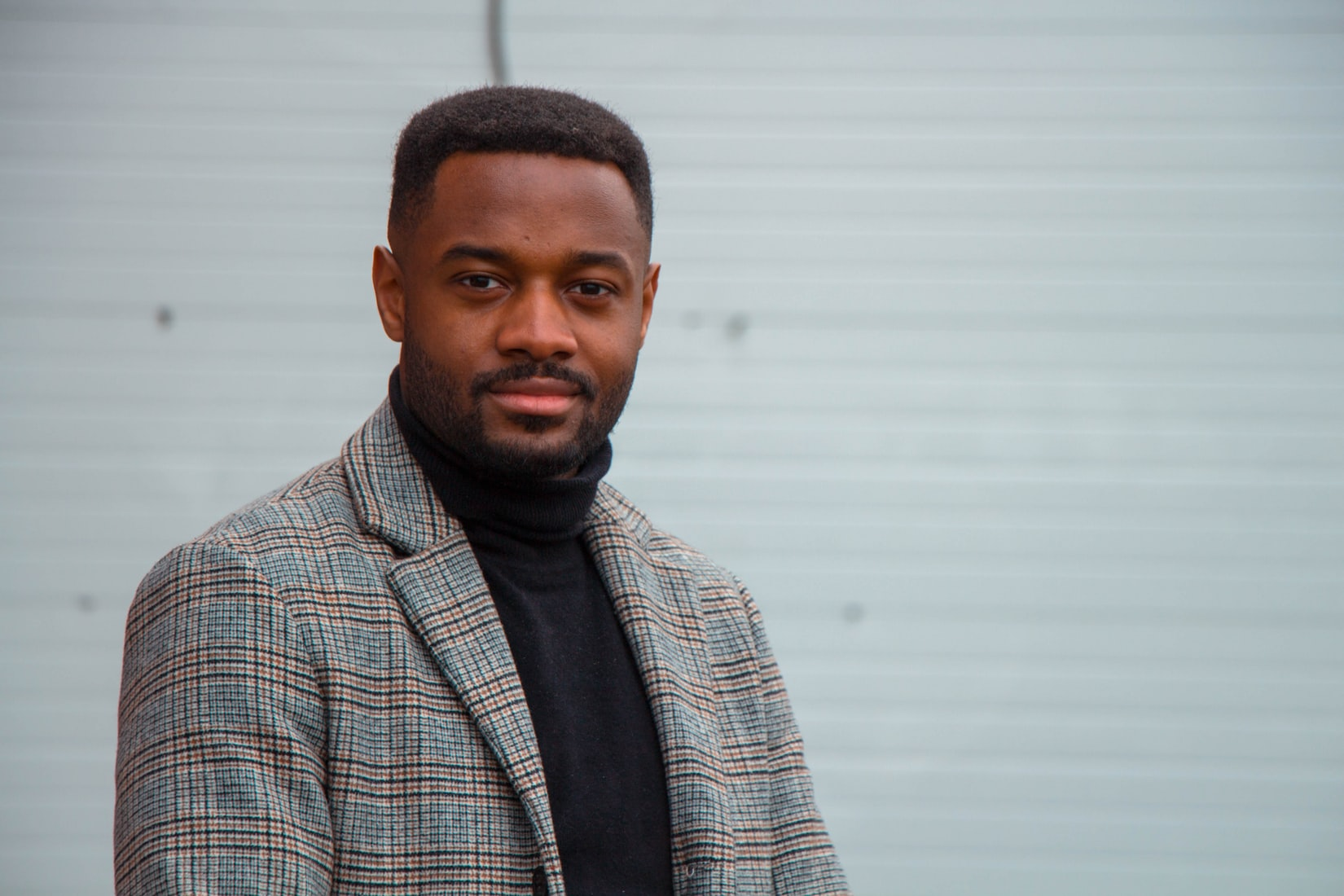 Close-up photography of black man wearing a black turtle neck shirt and gray blazer