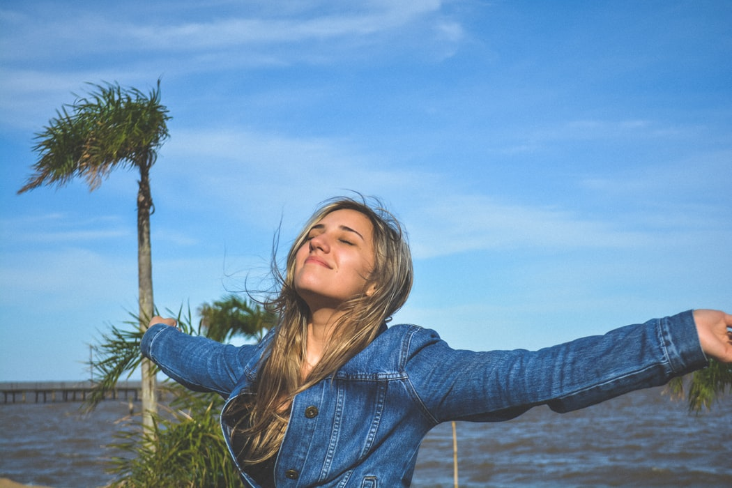 Happy blonde white woman spreading arms near body of water