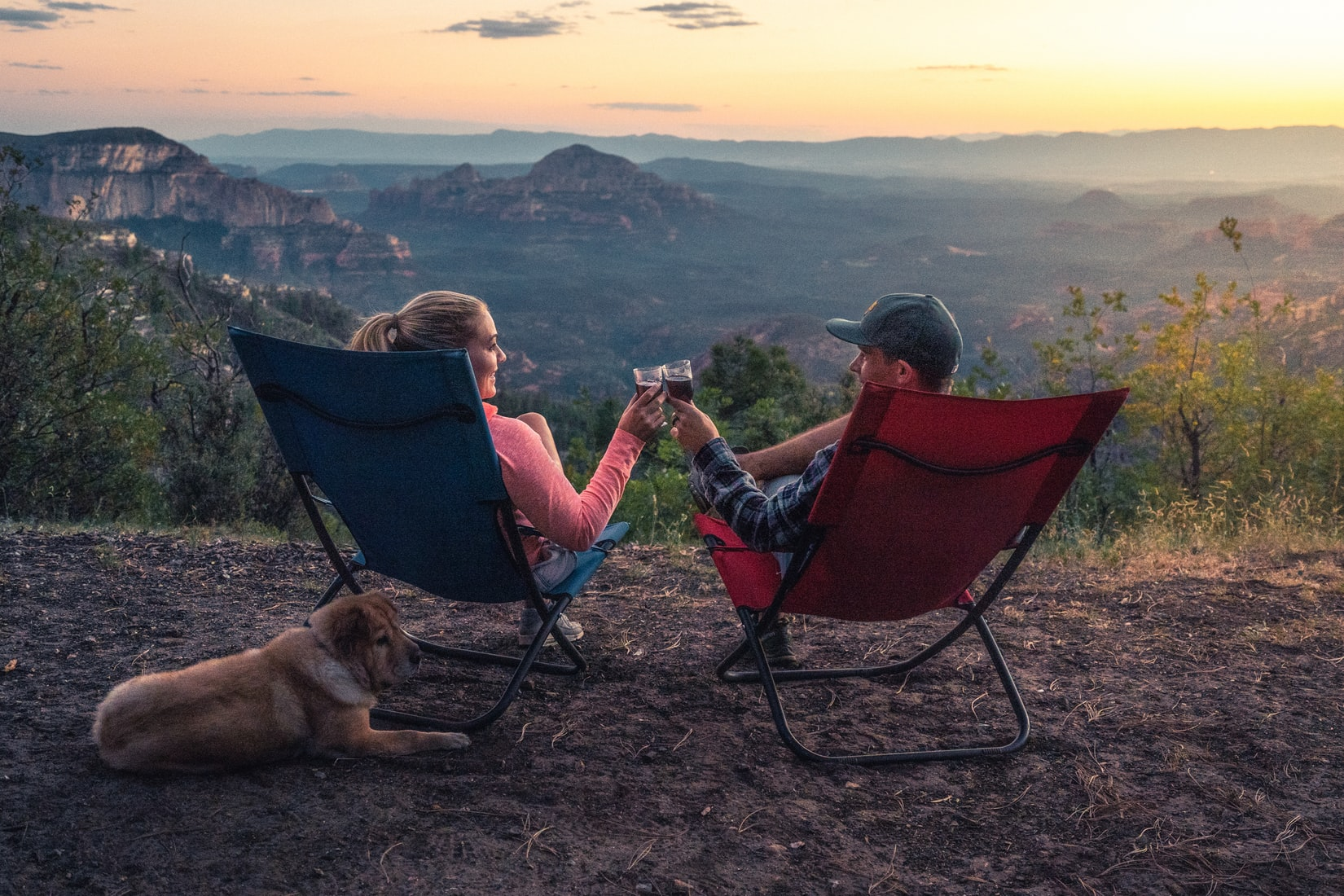 Man and woman sitting on camping chairs next to dog holding glasses in front of mountains