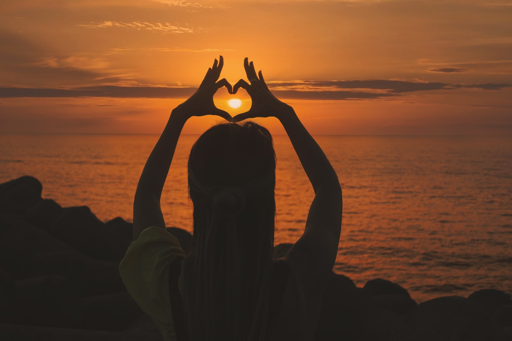 Silhouette of woman doing heart sign during sunset in front of body of water