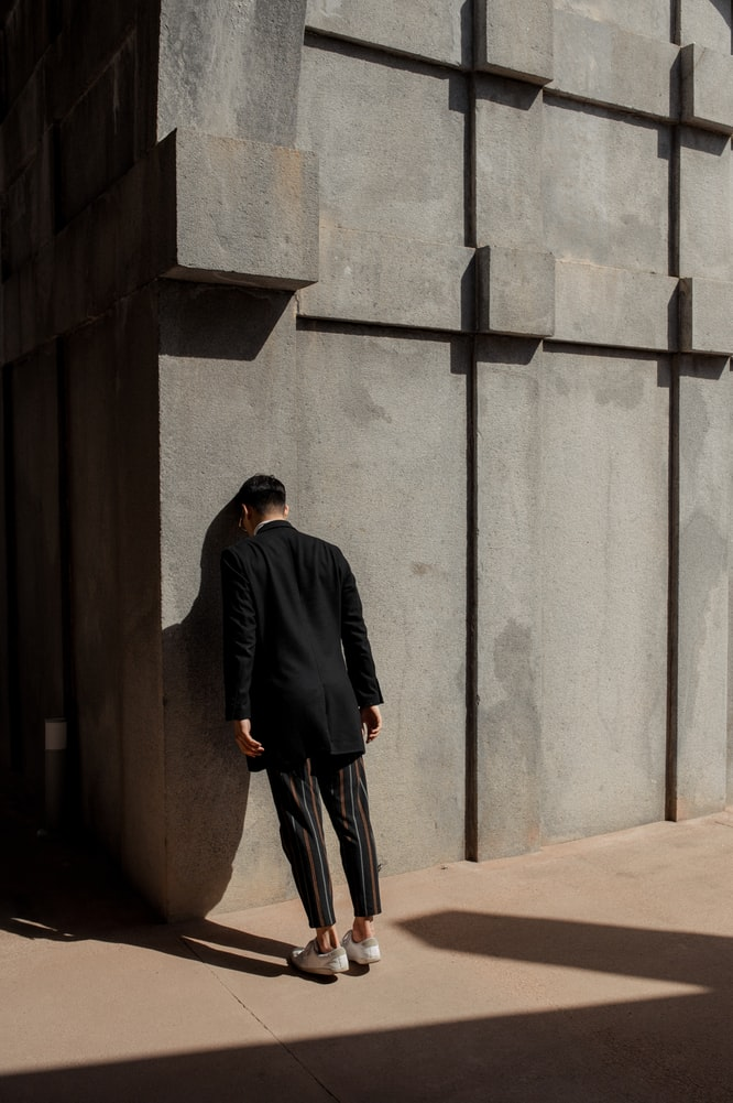 Worried man in black suit banging his head against stone wall