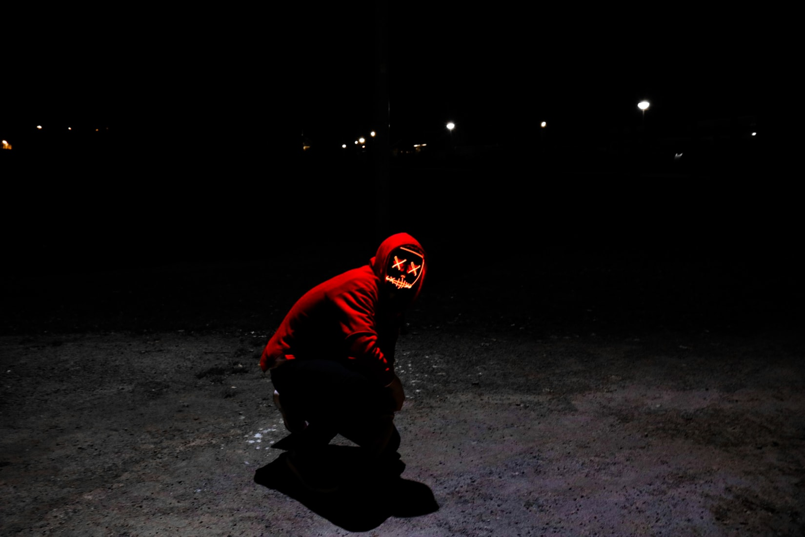 Psychotic man wearing red hoodie with mask squatting on pavement