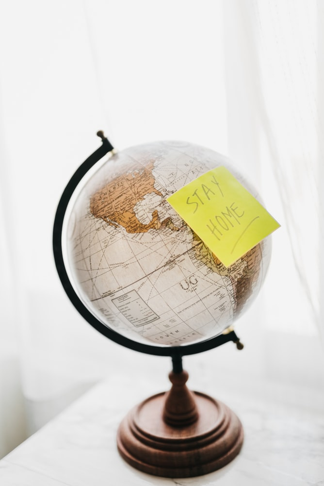 """Brown and black desk globe with yellow """"stay home"""" sticky note on top of it"""