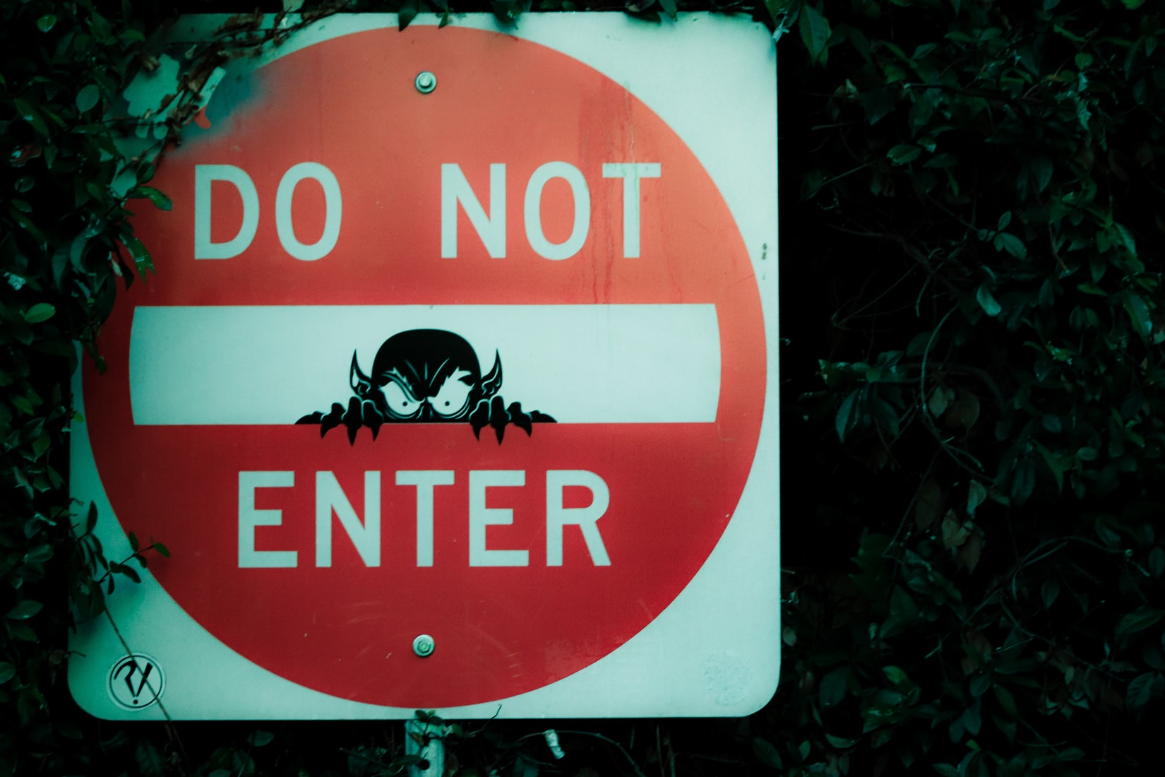 Red and white Do Not Enter street sign with drawing of demon between words