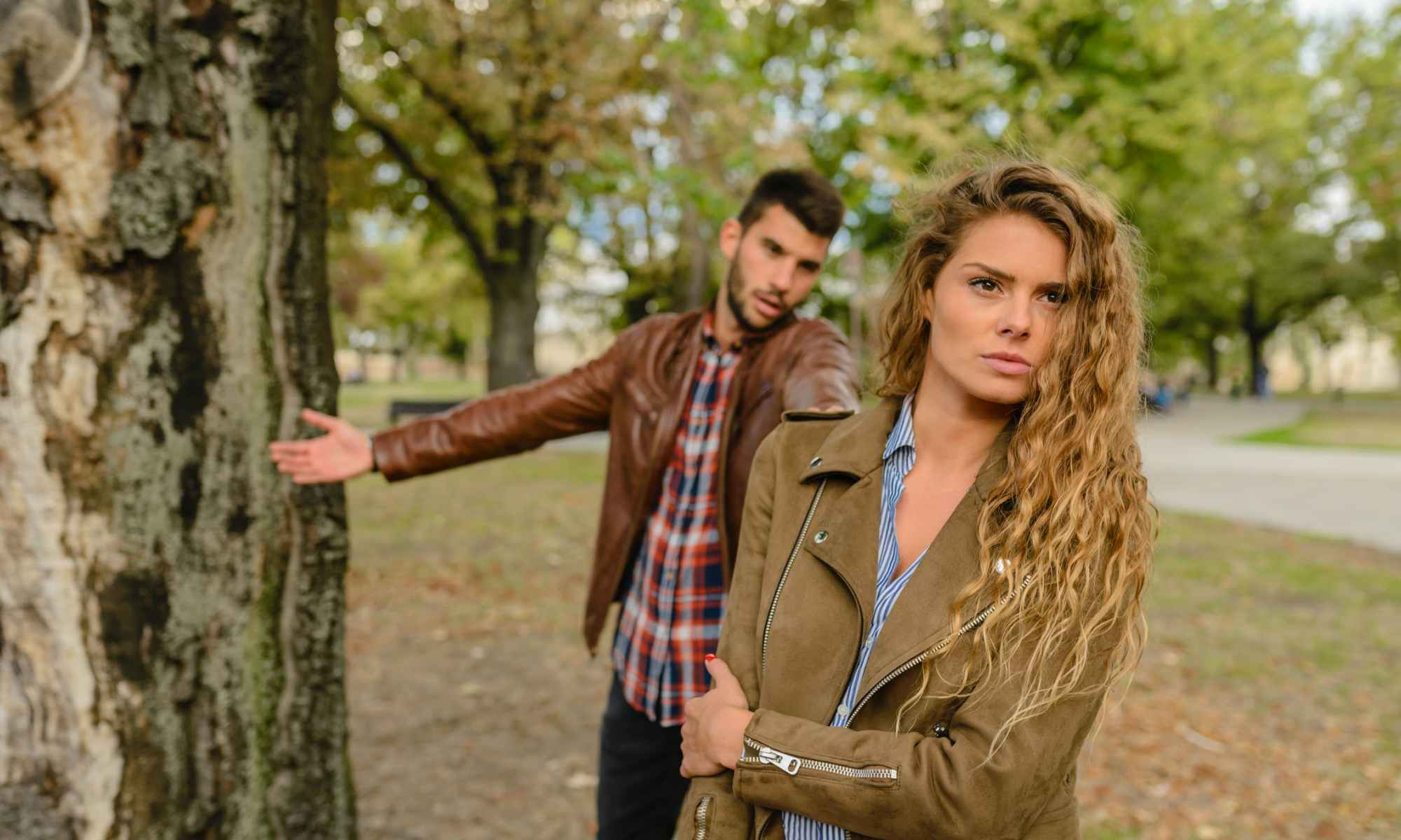Angry blonde woman walking away from backstabbing-man in park