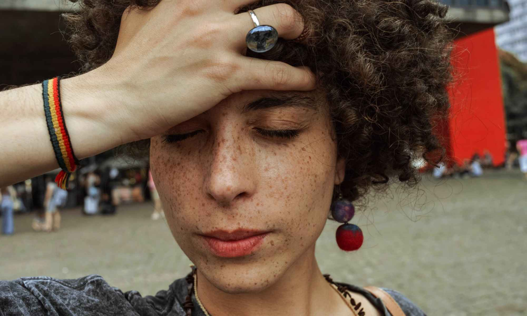 White woman with brown curly hair holding hand on forehead with eyes closed