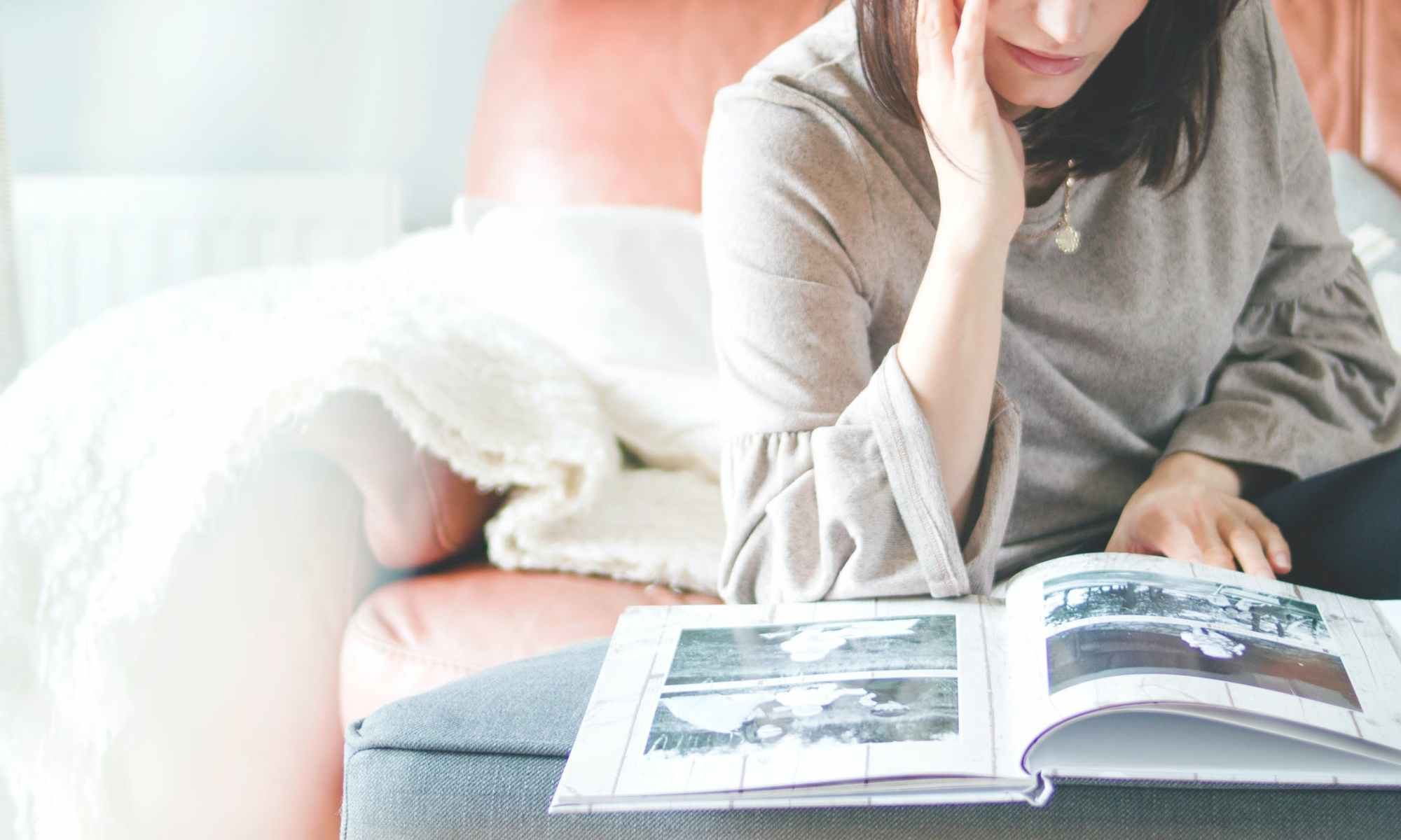 White woman sitting on pink couch looking at photo album