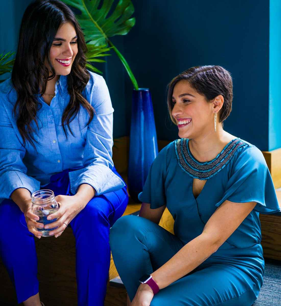Two brunette women talking and smiling next to blue vase with green plant