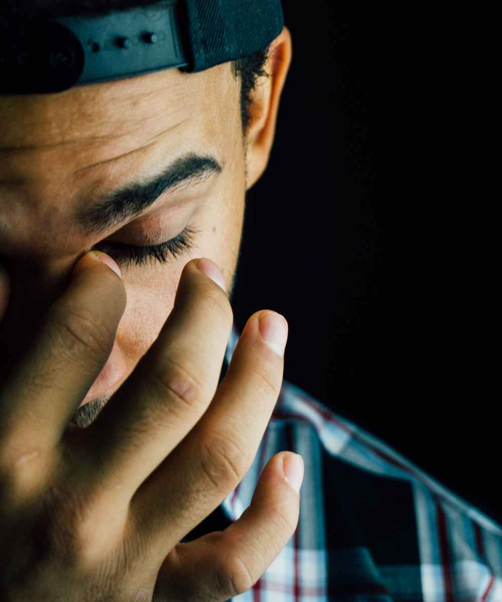 Tired black man with backwards cap on with hand on face
