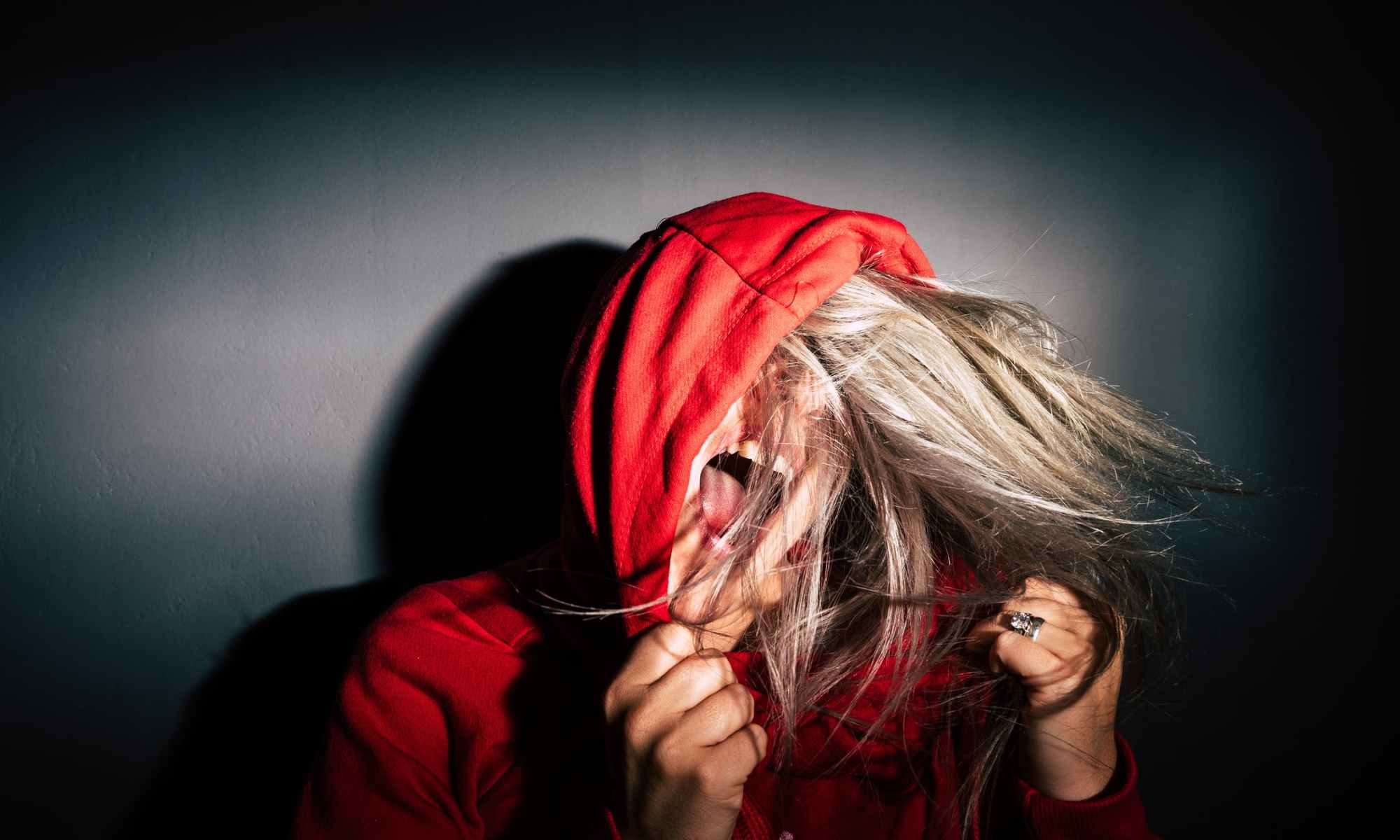 Angry blonde woman wearing red hoodie and yelling