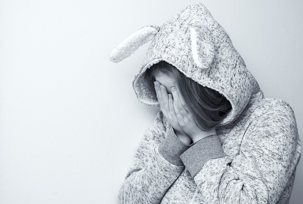 Depressed white woman wearing bunny ears outfit with hands covering face