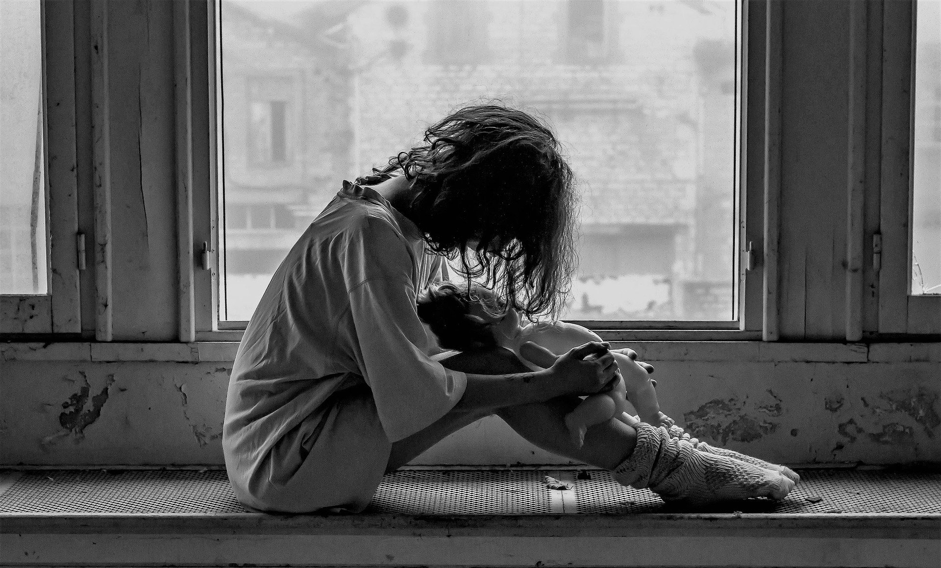 Feeling depressed - grayscale photo of depressed woman sitting next to window holding doll