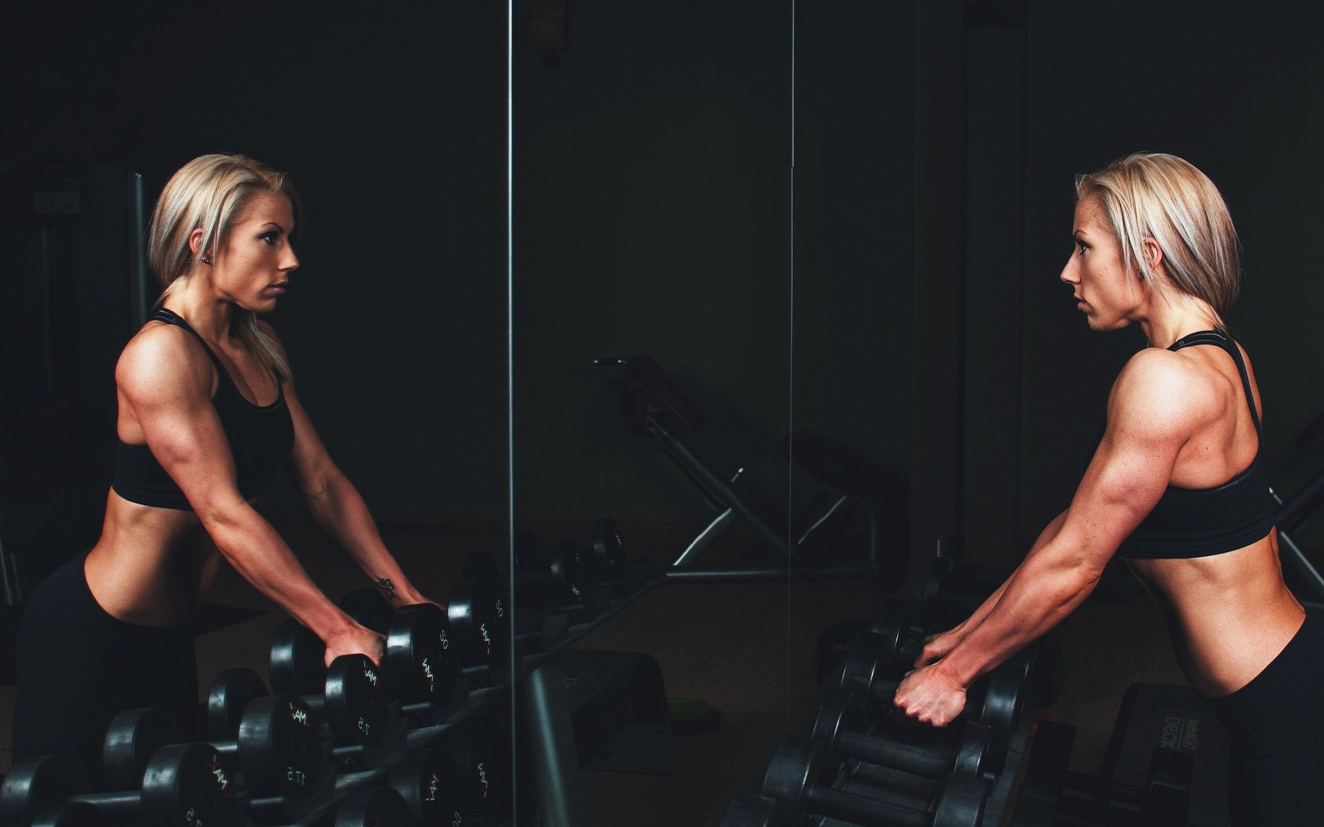 Blonde athletic girl holding weights in gym in front of mirror