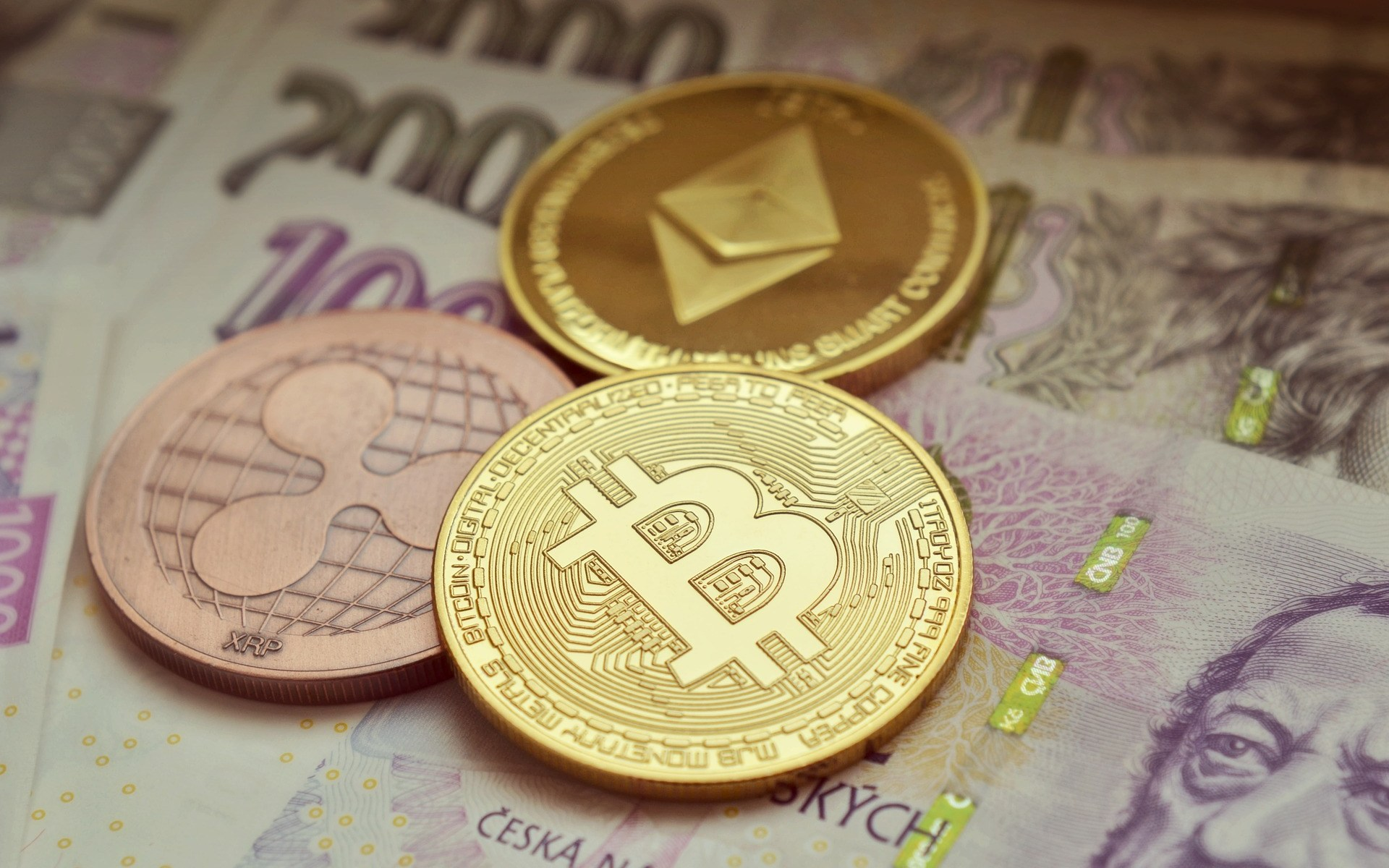 Bitcoin, Ethereum and XRP coins on fiat money