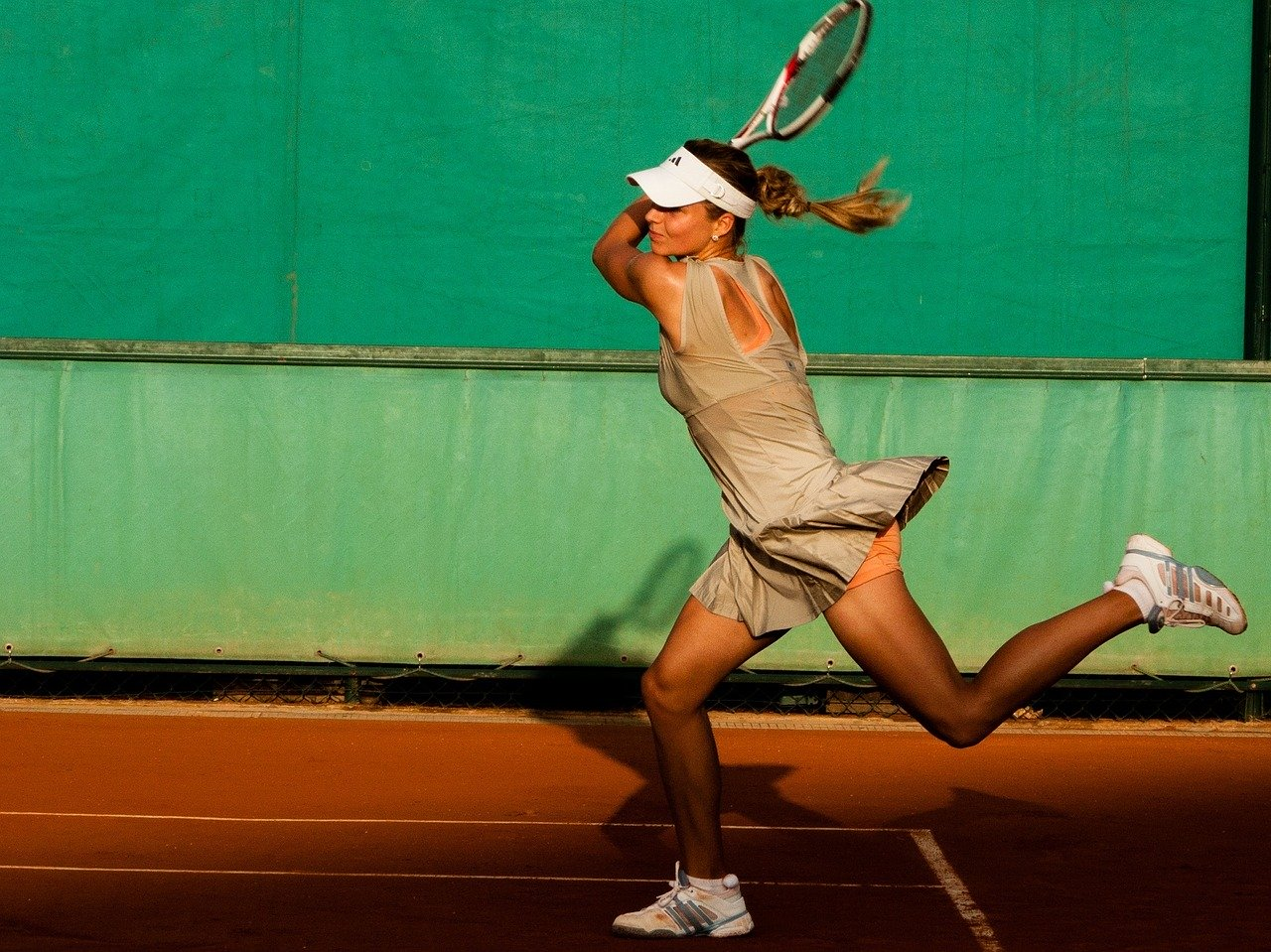 Female tennis player hitting backhand on red tennis clay court