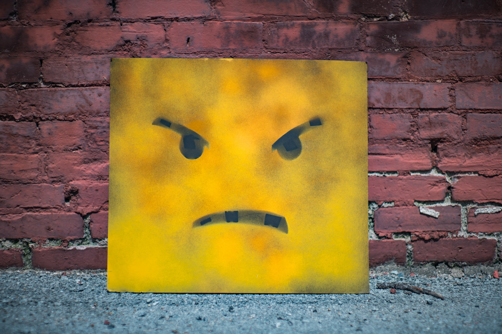Angry yellow and black smiley wall art against red brick wall