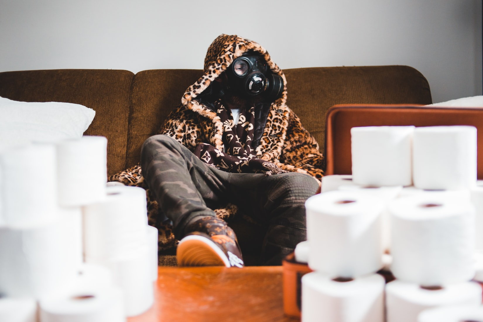 Person wearing cheetah coat with gas mask on sitting on couch with toilet paper on table