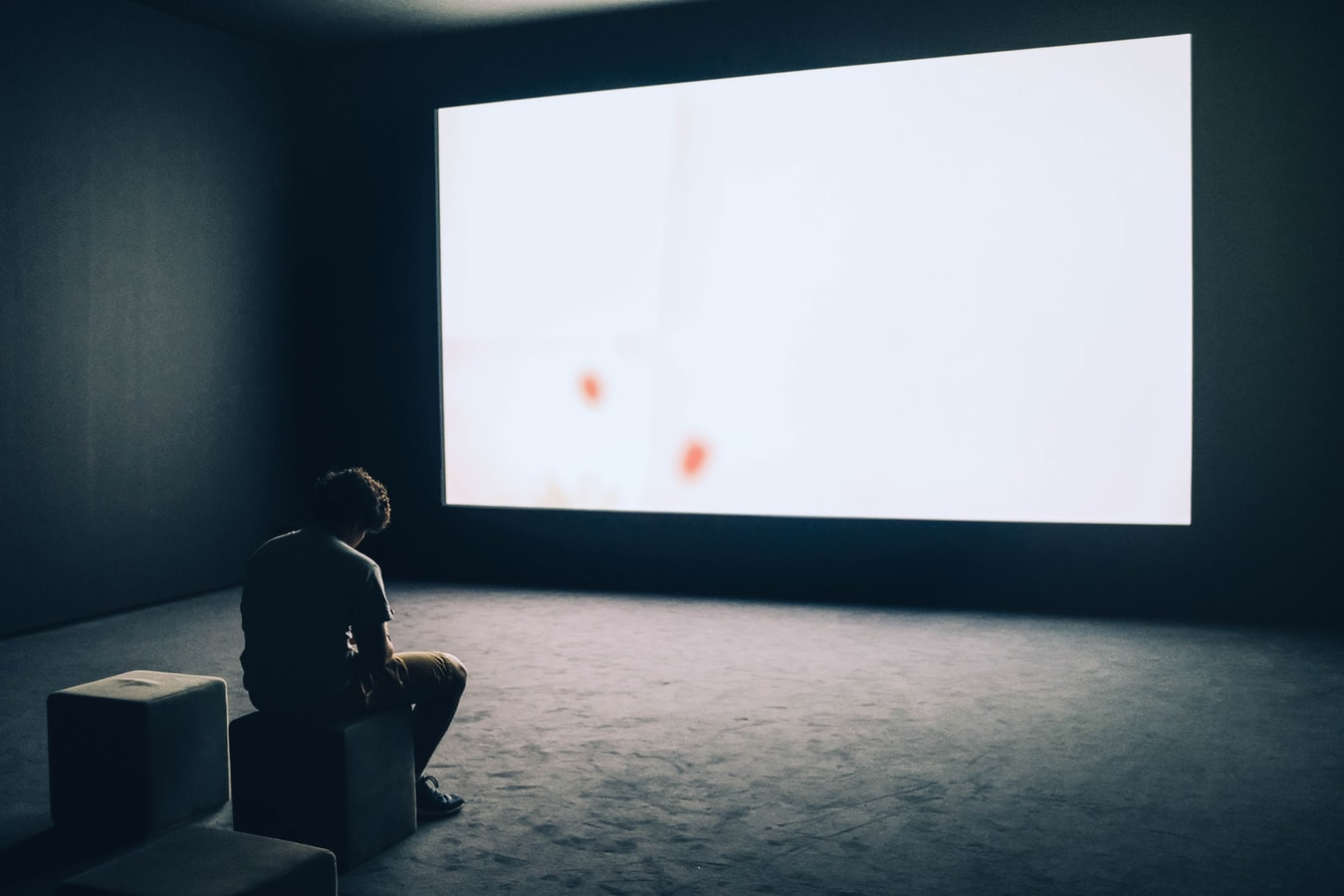 Lonely, sad man sitting in front of white projector screen