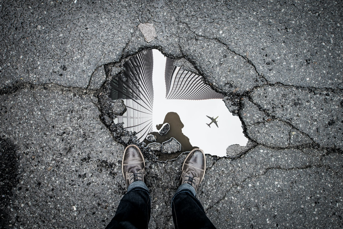Person standing in front of reflective puddle