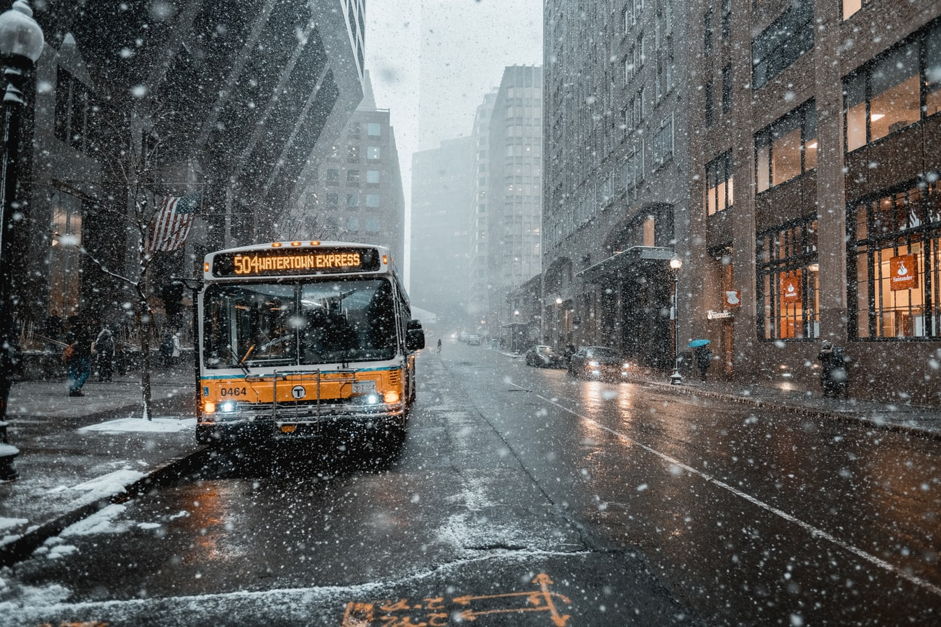 Yellow city bus on snowy road between buildings during daytime