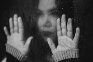 Isolation and depression: sad woman with hands on window