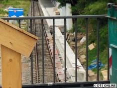 Durch den Zaun hindurchblickend sieht man die Bahnsteigelemente, welche zum neuen Aufgang führen werden.