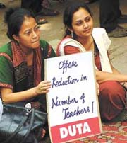 Teachers protest outside the UGC building on Monday against two circulars issued by the commission that seek to increase the teachers' workload and decrease their numbers