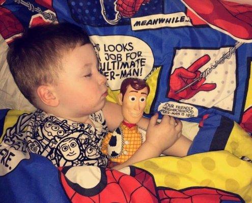 toddler sleeping in bed cuddling toys