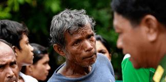 Zwei Muslime hören einem hochrangigen Offizier, Lieutenant General Hla Min, während seines Besuchs von Opfern der Unruhen im Dorf Pauk Taw in der Nähe von Thandwe, zu.