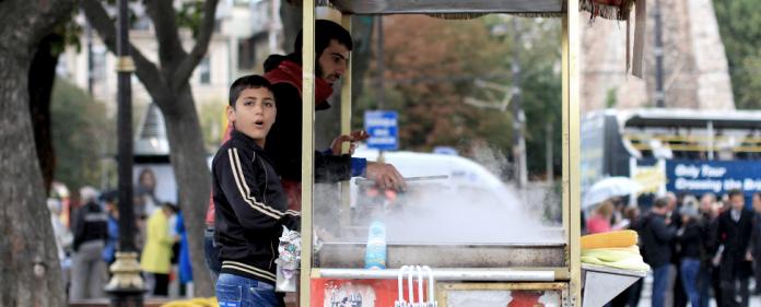 Zwei Jungen verkaufen am Sultanahmet-Platz gekochte Maiskolben.