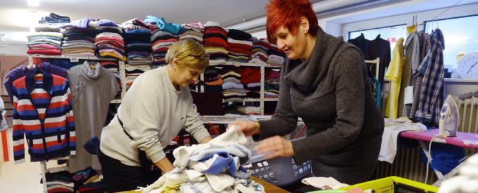 Silvia Fisovic (l) und Sigrid Bluekens, Teilnehmerinnen des Arbeitsprojekts des Tagestreff für Frauen (TafF) in Karlsruhe (Baden-Württemberg), arbeiten am 31.01.2014 in der dortigen Kleiderkammer. Beide waren bis vor kurzem noch auf Wohnungssuche.