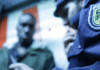 In einer nachgestellten Szene kontrolliert ein Polizist einen farbigen Passanten.