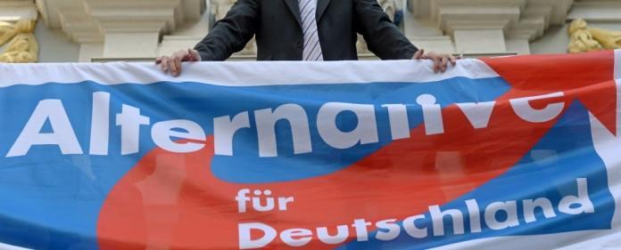 Der Bundesvorsitzende der Partei Alternative für Deutschland (AfD), Bernd Lucke, steht am 28.08.2013 auf einer Wahlkampfveranstaltung seiner Partei in Leipzig (Sachsen) auf einem Balkon mit dem Parteilogo.