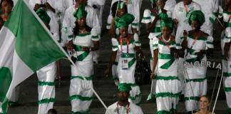 nigeria's flag bearer sinivie boltic holds the national flag as he leads the contingent in the athletes parade during the opening ceremony of the london 2012 olympic games at the olympic stadium july 27, 2012.