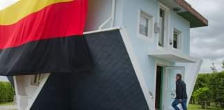 """Mitarbeiter der Touristenattraktion """"Die Welt steht Kopf"""" haben am 23.06.2014 in Trassenheide auf der Insel Usedom (Mecklenburg-Vorpommern) eine Deutschlandflagge an das kopfstehende Haus angebracht. Die rund neun mal vier Meter große Flagge hängt, ganz im Sinne des auf dem Dachfirst stehenden Hauses, mit den Flaggenfarben """"Gold-Rot-Schwarz"""" falsch herum. Die Flagge soll bis zum Finalspiel als Glücksbringer am Haus hängen bleiben."""