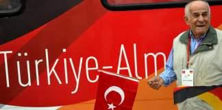 """Ein älterer Mann, mit der türkischen Flagge und der deutschen Flagge vor dem """"Deutschland-Zug"""" - (cihan)"""