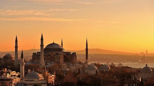 Die prächtige Hagia-Sophia prägt das Bild Istanbuls. Das Bild zeigt die Metropole am Bosporus bei Sonnenaufgang, die Hagia-Sophia erstrahlt in gelb-orange.
