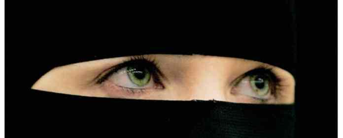 Eine Frau trägt einen schwarzen Niqab, der bis auf die Augen das gesamte Gesicht verdeckt.