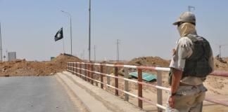 Ein kurdischer Kämpfer steht etwa 20 Meter von einer IS-Straßensperre nahe Kirkuk. Die schwarze IS-Fahne ist deutlich zu erkennen.