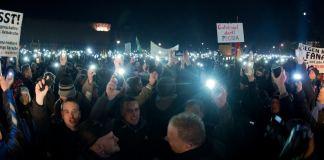 Teilnehmer einer Kundgebung der Pegida in Dresden (Sachsen) halten am 08.12.2014 zum Abschluss der Kundgebung leuchtende Mobiltelefone in die Höhe