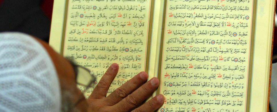Ein alter Mann liest den Koran.