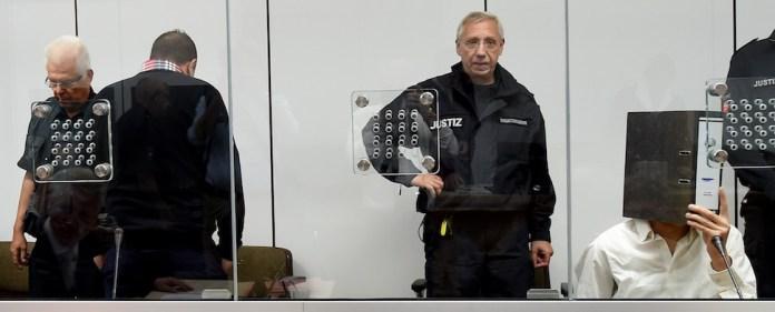 Die beiden Angeklagten Ebrahim H. B. (26, 2.v.l.) und Ayoub B. (27, r, verdeckt von einem Aktenordner) sitzen zu Beginn der Verhandlung am 03.08.2015 in einem mit Sicherheitsglas abgetrennten Raum im Gerichtssaal des Oberlandesgerichts in Celle (Niedersachsen). Die zwei IS-R¸ckkehrer stehen vor Gericht, weil sie laut Anklage Ende Mai 2014 ¸ber die T¸rkei nach Syrien reisten und sich dort der Terrororganisation Islamischer Staat (IS) anschlossen.