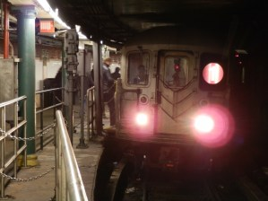 A 1 train takes on passengers as it waits to return to the uptown track.