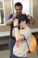 Man putting VR Glasses on a teen