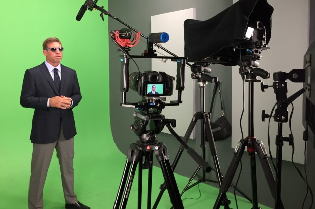 A behind the scenes looks at Dallas Cowboy's Troy Aikman filming green screen video interviews in a studio.