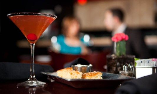 Editorial food photography in Dallas of a couple eating dinner with a martini in the foreground