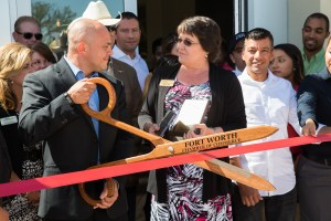 Photography of a man with giant scissors that say Fort Worth at a ribbon cutting event .