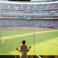 A kid at a sporting event for the Texas Rangers looking at the baseball field out a window.