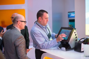 Men playing on tablets at a trade show