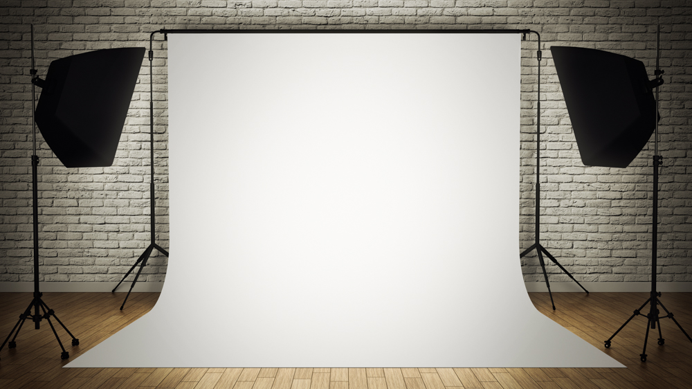 A white backdrop sitting in front of bricks with video lights illuminating it.